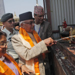 Nepalese Prime Minister Khadga Prassad Oli, center, lights a butter lamp to initiate reconstruction work in Swayambhunath stupa that was destroyed in last years's earthquake in Kathmandu, Nepal, Monday, April 25, 2016. Prime Minister Khadga Prasad Oli  has announced the start of reconstruction of heritage sites in the capital that were damaged by an earthquake that devastated the country one year ago. (AP Photo/Niranjan Shrestha)